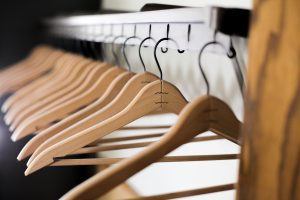 Wooden hangers lined up in a closet