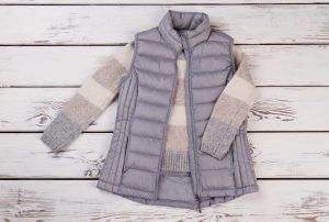 Combination of down vest and sweater for chill winter weather. New collection items on a wooden shelf. Great combo for a winter vacation.