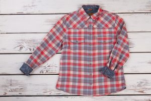 Stylish flannel plaid shirt on wooden shelf. Metal buttons and country pattern. Women's fashion trends. Also a great layering piece for a winter vacation.