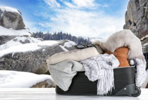Open suitcase with stuff for winter vacation on table against mountain landscape - packing for winter vacation.