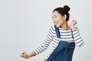 Portrait of brunette Caucasian hipster girl dancing against gray blank wall with smile, rejoicing good mood. Student female with hairbuns having fun while dancing to some pleasant music indoors