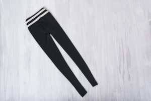 Black leggings on wooden background. Fashionable concept. Great for layering on a winter vacation.