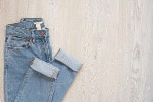 Blue jeans on a wooden background. Flat lay of female styled look. Top view. Shopping Concept. Fashion Outfits. Also great for packing on a trip.