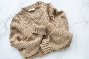 picture of a sweater laying flat which is a great piece to bring on a winter vacation.
