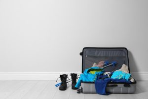 Open suitcase with warm clothes for winter vacation on wooden floor. Space for text