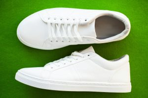Pair of new stylish white sneakers on green background