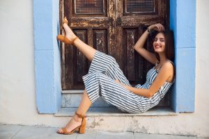 Young stylish woman posing in old wooden doorway on the street. Fashion and lifestyle concept wearing overalls and heels.