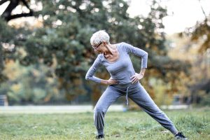 Older woman stretching in the grass getting ready for a walk wearing workout wear. Joggers and a matching grey top.