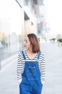 young woman wearing blue jeans overalls exploring the street of downtown,Shandong province,China