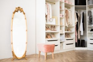Stylish closet space with antique gold full length mirror and pink velvet plush sitting stool