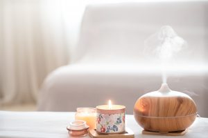 Modern oil aroma diffuser in the living room on the table with burning candles . The concept of refreshing and purifying the air in the house. A work from home essential fragrance.