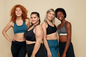 Diversity. Group Of Women Of Different Race, Figure And Size Portrait. Smiling Multi-Ethnic Female In Sportswear Posing On Beige Background. Body Positive As Lifestyle.