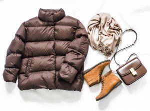 Women's brown down jacket, cashmere scarf, leather shoulder bag, oxford suede boots on a light background, top view. Autumn, winter women's clothing fashion concept