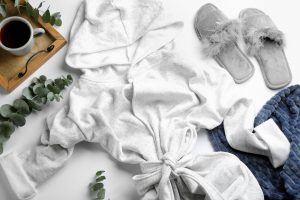 Composition with fluffy slippers and robe on white background, flat lay. Comfortable work from home essential outfit