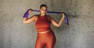 Plus size woman working out with resistance band. Healthy female in fitness attire exercising outdoors.