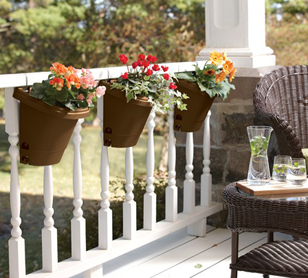 Planters hanging over a balcony rail.