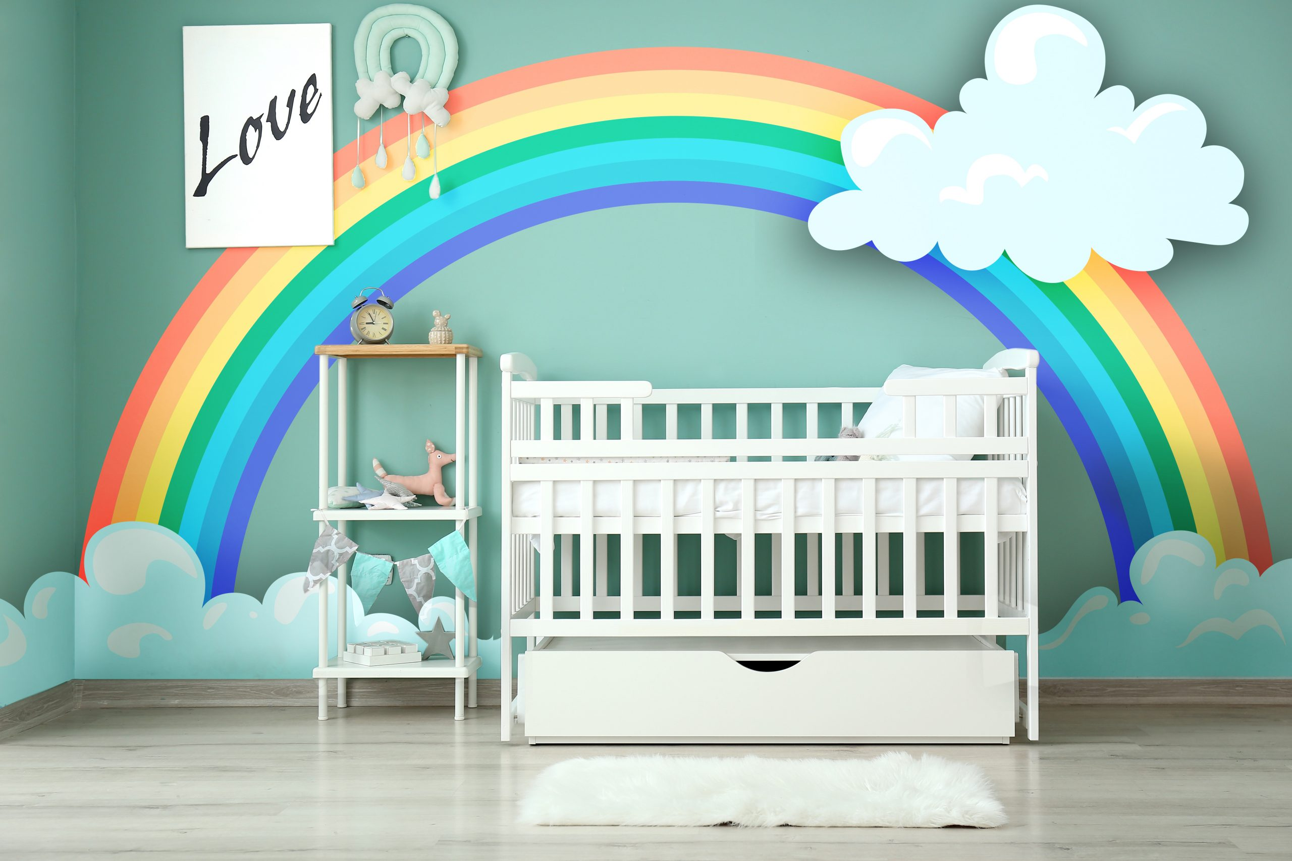 Modern baby room with crib and painting of rainbow on wall