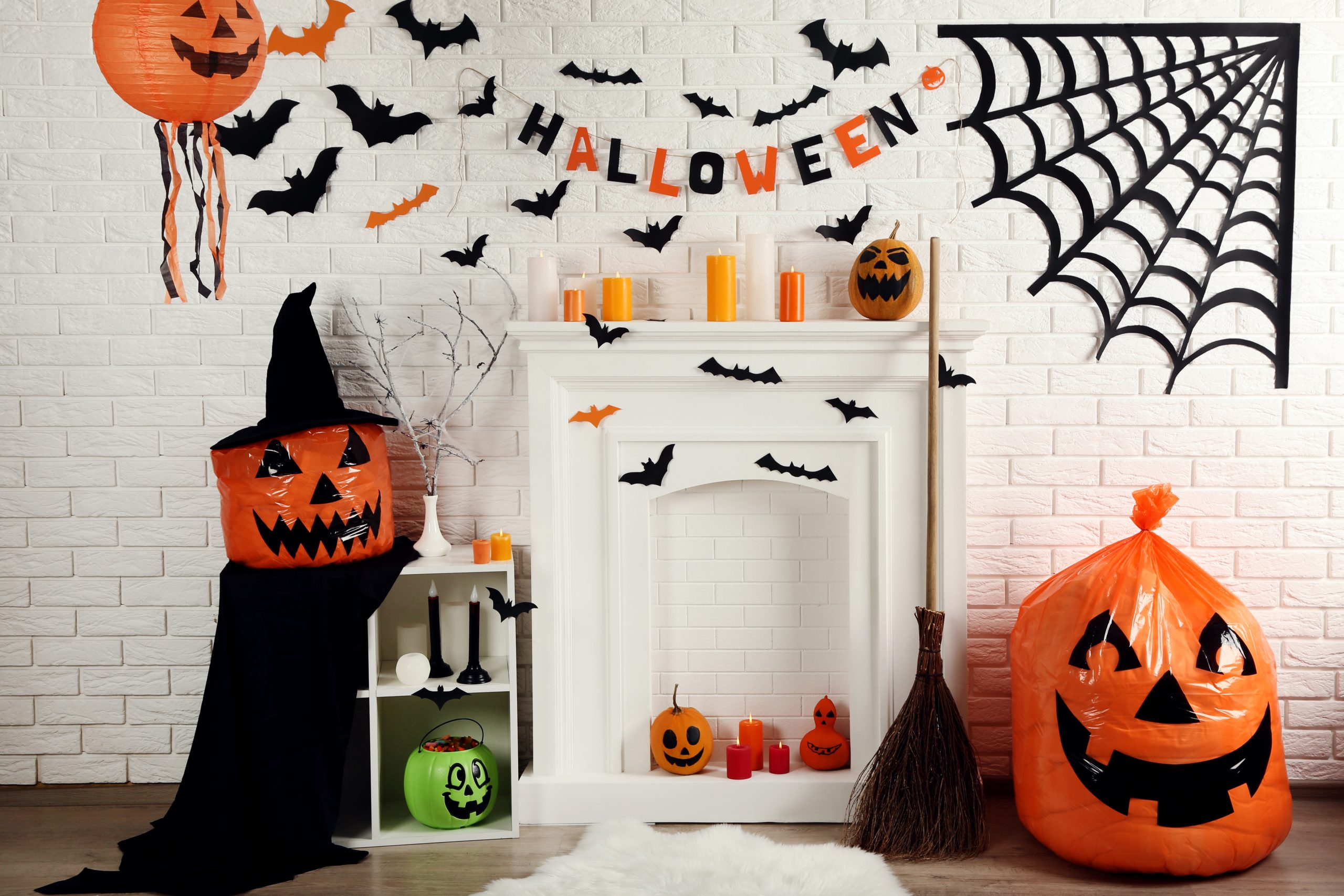 Halloween decorations on white fireplace with orange pumpkins