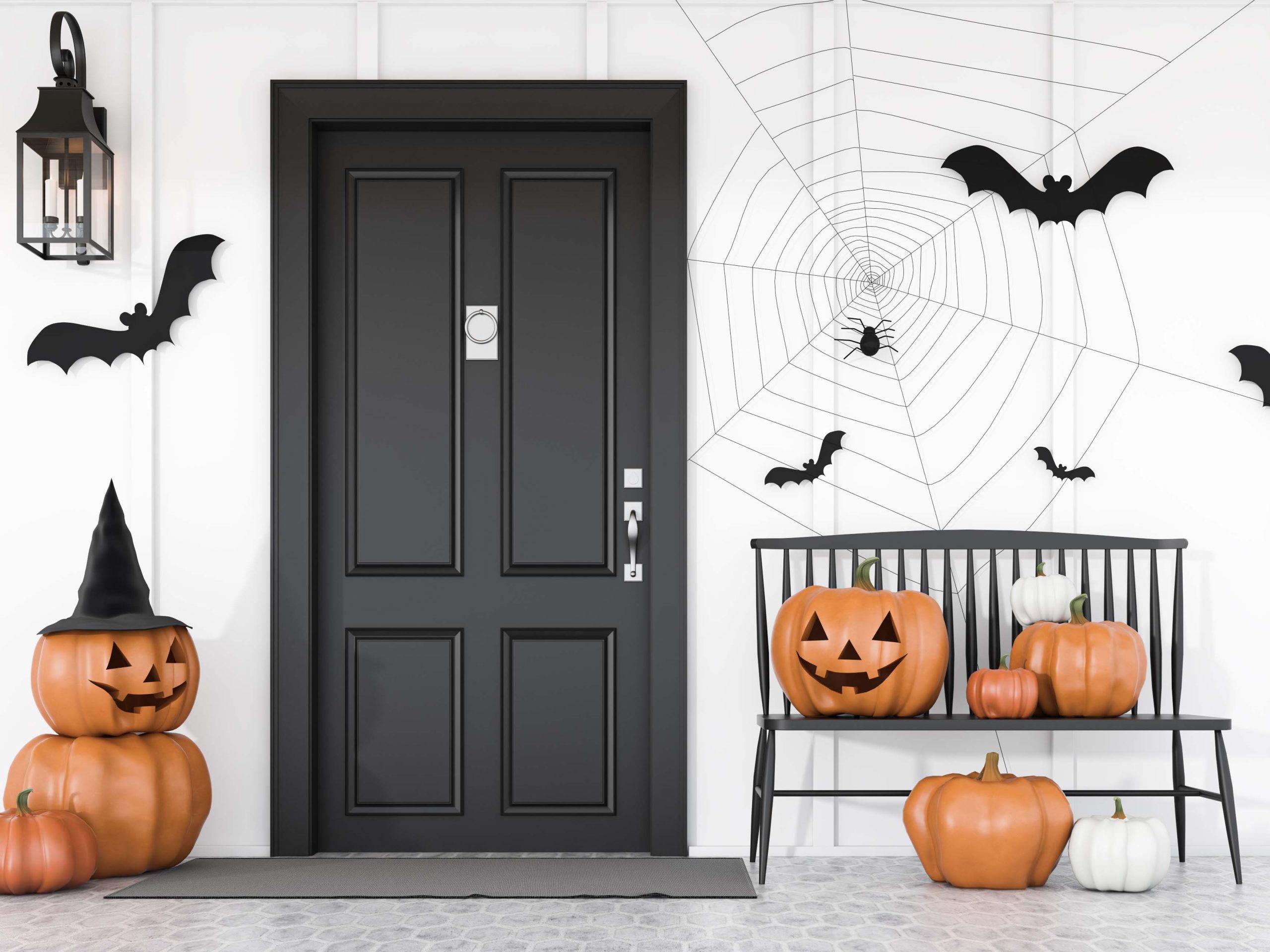 Carved pumpkins near black house door